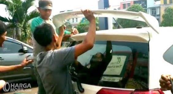 Gambar ini menunjukkan beberapa orang sedang memasang spoiler mobil