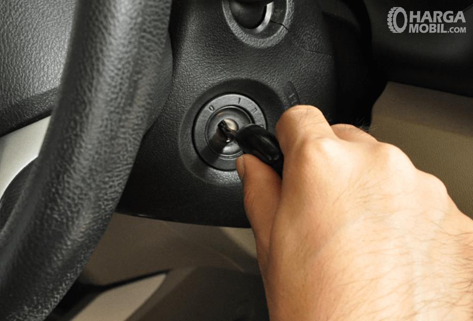 Gambar ini menunjukkan sebuah tangan memgang kunci dan akan memutarnya untuk menyalakan mesin