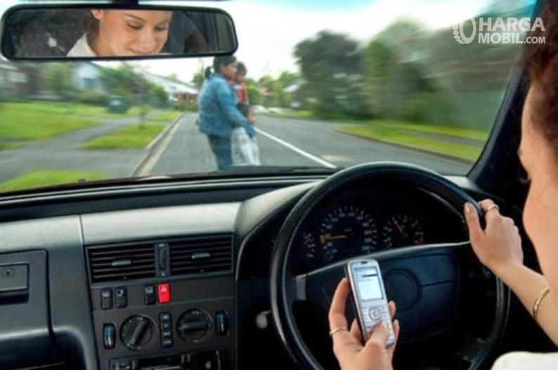 Gambar ini menunjukkan seorang pengemudi wanita sedang mengemudi sambil lihat ponsel