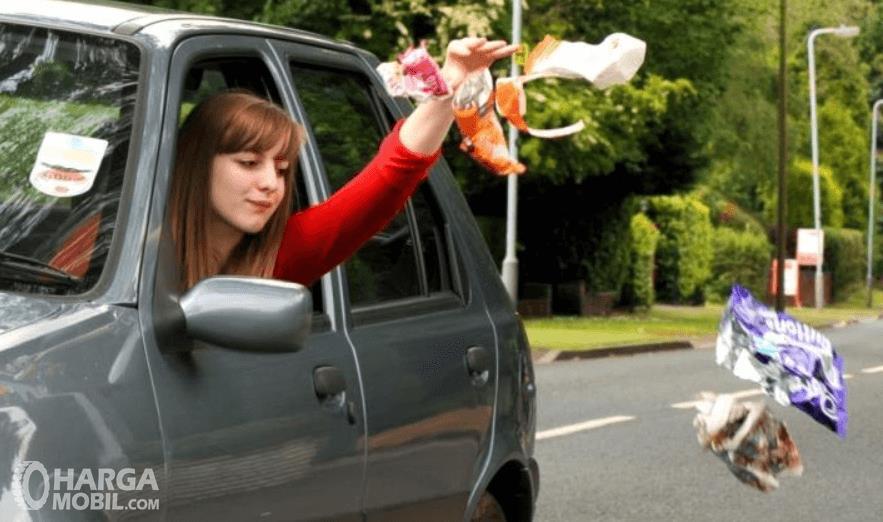 Gambar ini menunjukkan seorang wanita membuang sampah keluar dari mobil