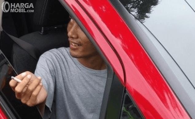 Gambar ini menunjukkan seorang pria sedang merokok di dalam mobil