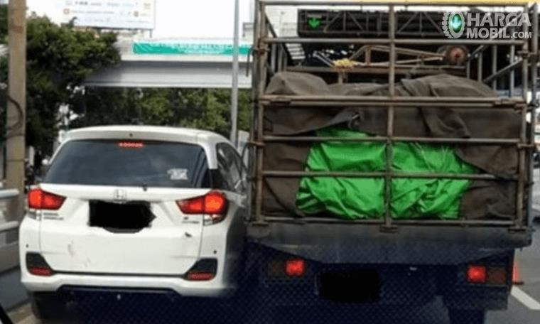 Gambar ini menunjukkan mobil truk dan mobil keluarga saling berhimpitan