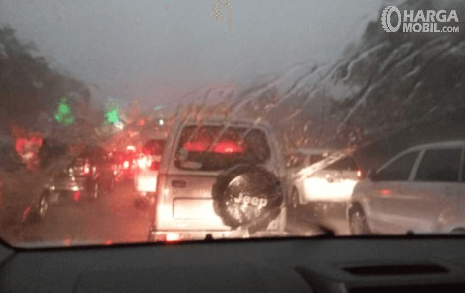 gambar ini menunjukkan mobil melaju dalam kondisi hujan