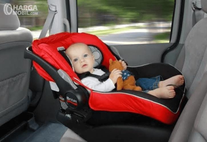 Gambar ini menunjukkan Child Seat yang sedang diduduki oleh balita