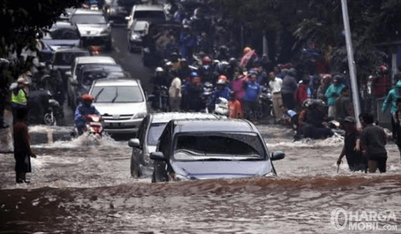 Gambar ini menunjukkan banyak mobil sedang antri ingin melewati banjir