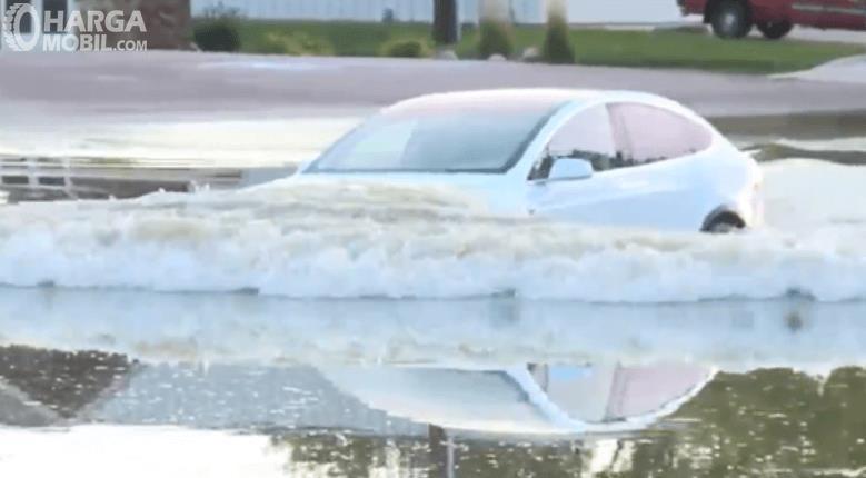 Gambar ini menunjukkan mobil warna putih menerjang banjir