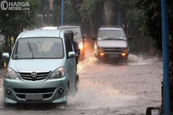 Gambar ini menunjukkan beberapa mobil menerjang banjir