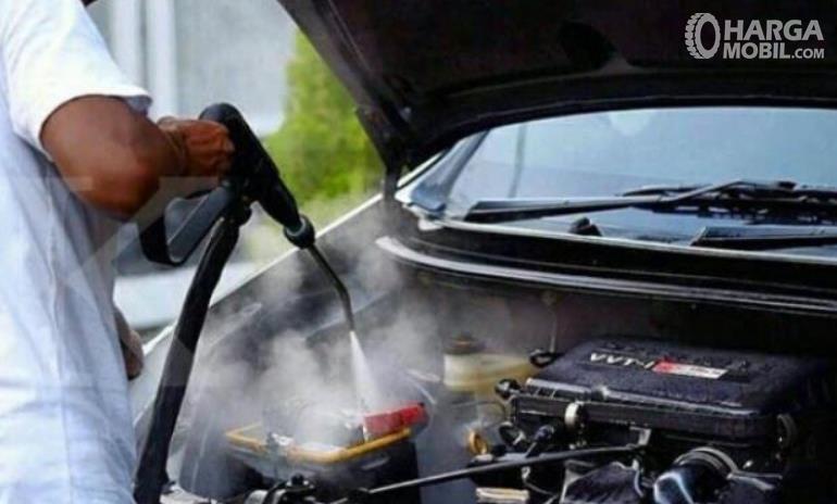 Gambar ini menunjukkan mesin mobil sedang disemprot uap