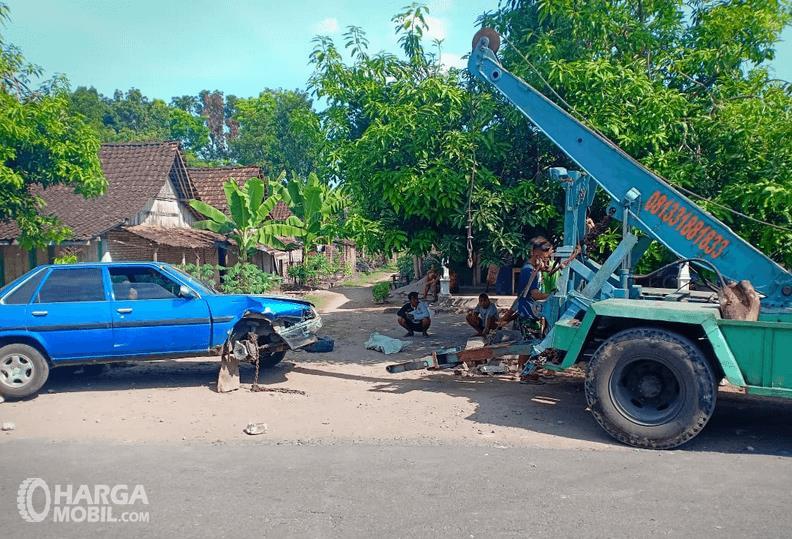 Gambar ini menunjukkan derek mobil model boom dengan mobil warna biru