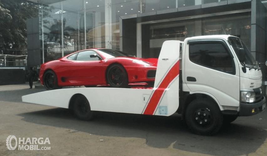 Gambar  ini menunjukkan derok mobil model hidrolik dengan mobil merah di belakangnya
