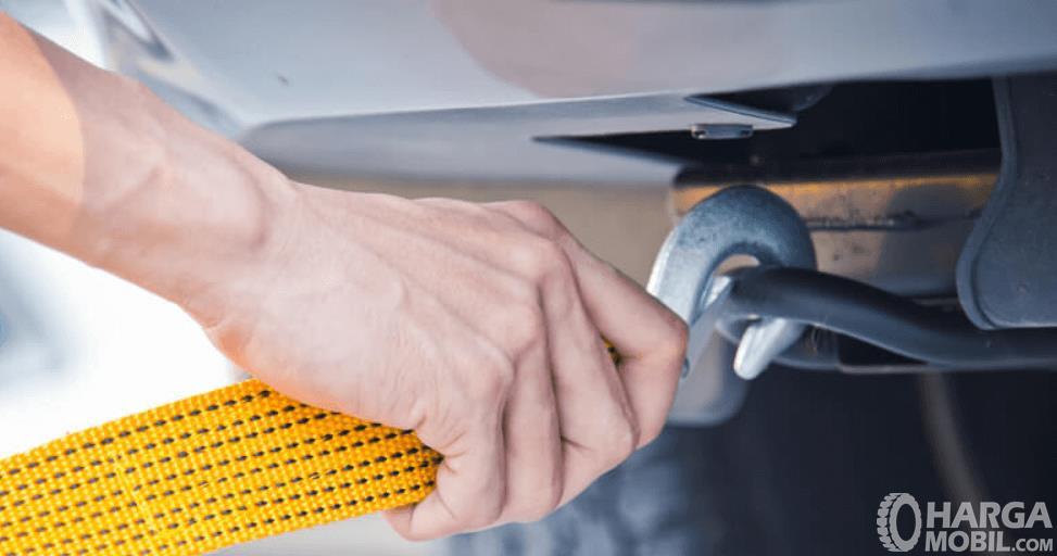 gambar ini menunjukkan sebuah tangan memasang tali untuk menderek mobil