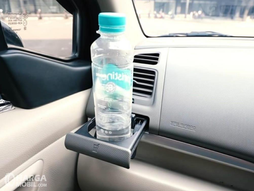 Gambar ini menunjukkan sebuah botol minuman pada cup holder dekat ac mobil