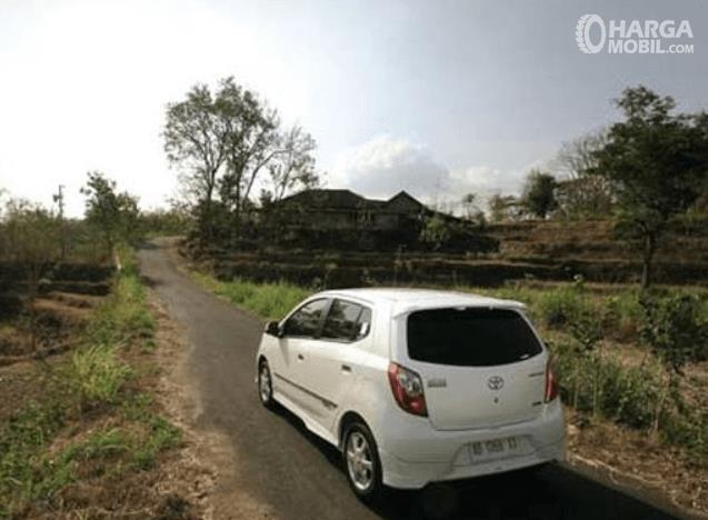 Gambar ini menunjukkan sebuah mobil warna putih melaju di jalan sempit