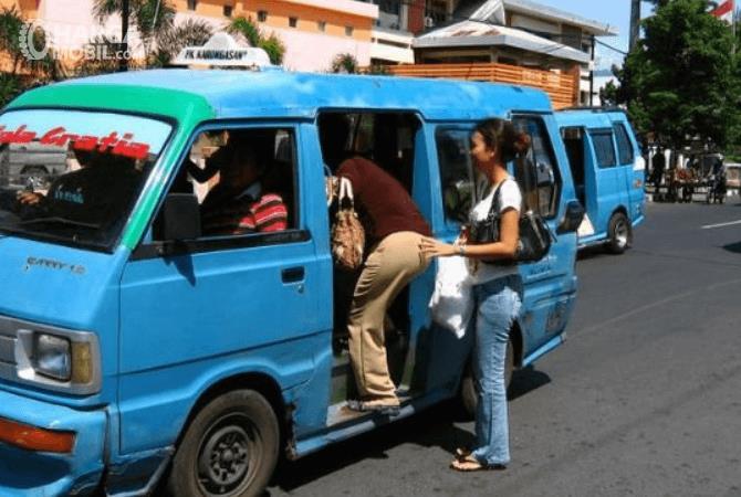 Gambar ini menunjukkan beberapa orang sedang naik angkutan umum warna biru