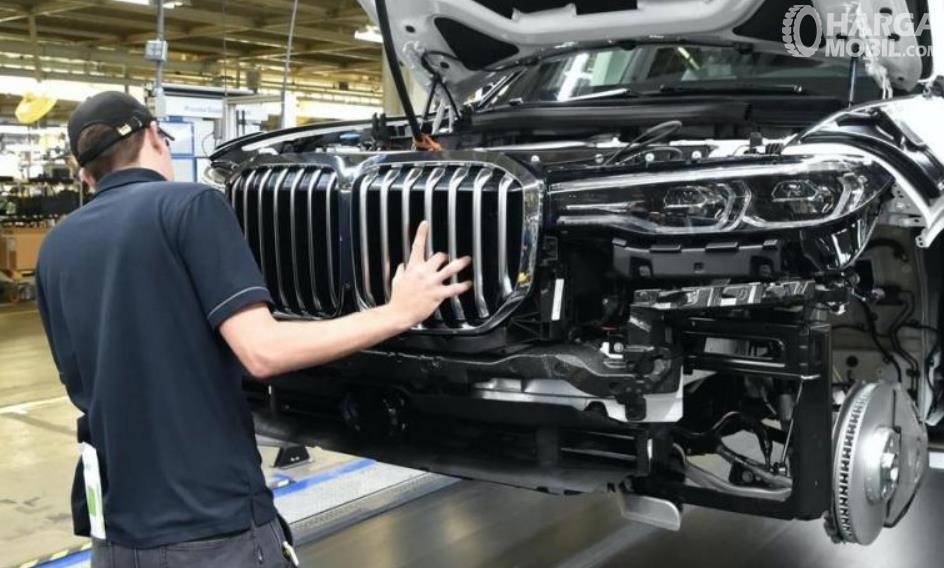 Gambar ini menunjukkan seorang pria sedang merakit mobil BMW