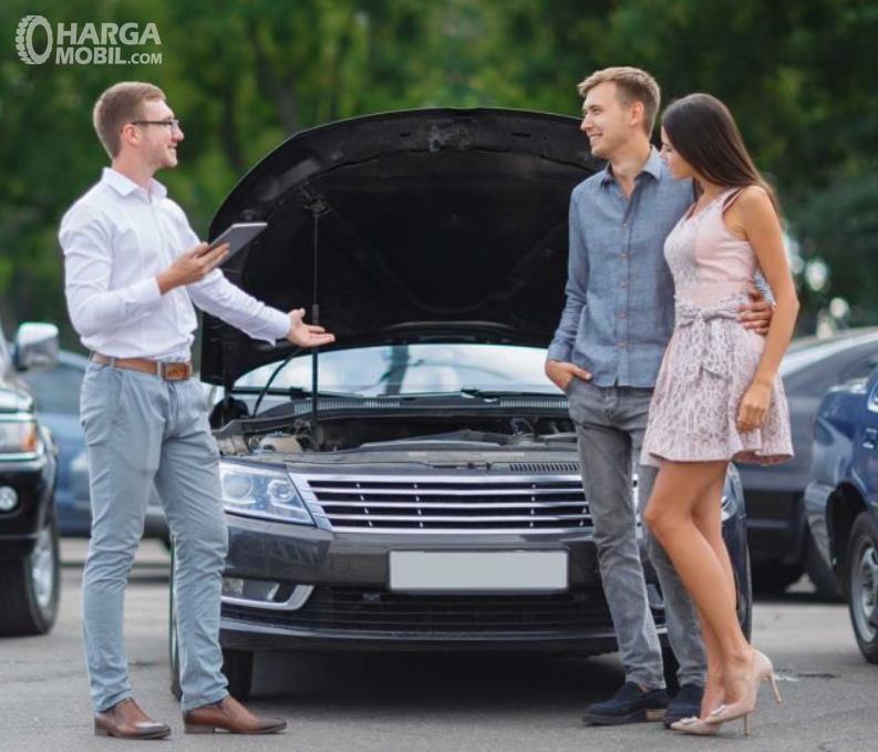 Gambar ini menunjukkan 3 orang berdiri di depan mobil