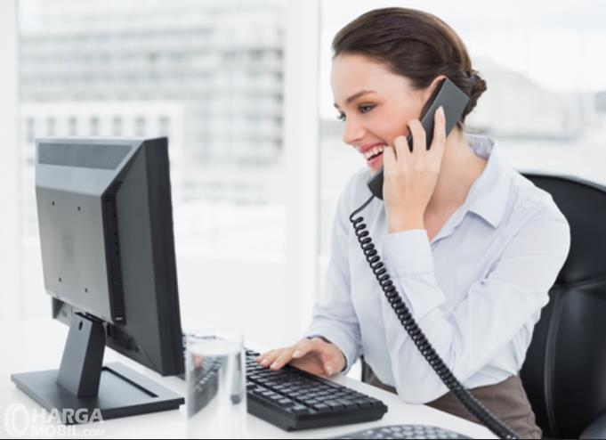 Gambar ini menunjukkan seorang wanita sedang menelpon dan melihat laptop