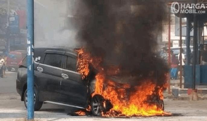 Gambar ini menunjukkan mobil hitam yang terbakar