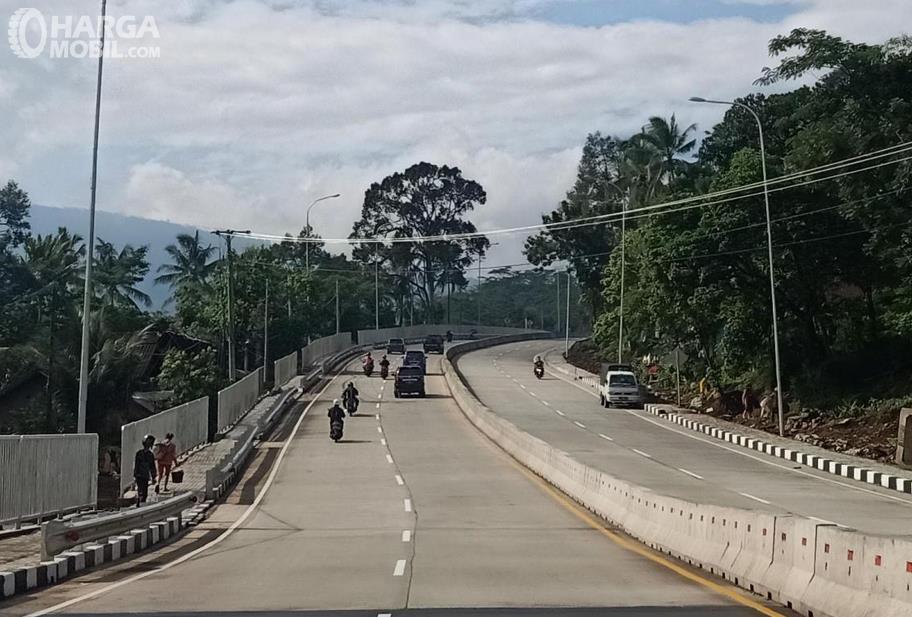 Gambar ini menunjukkan jalanan dengan beberapa mobil dan motor serta pembatas tengah