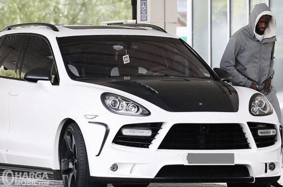 Gambar ini menunjukkan  Yaya Toure berada di samping mobilnya