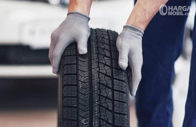 Gambar ini menunjukkan 2 buah tangan memegang ban mobil