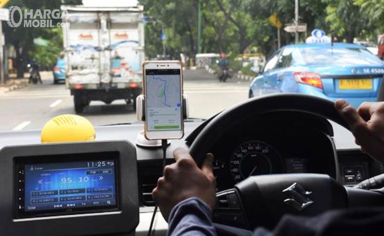 Gambar ini menunjukkan seorang pengemudi mobil memegang setir dengan melihat map di HP