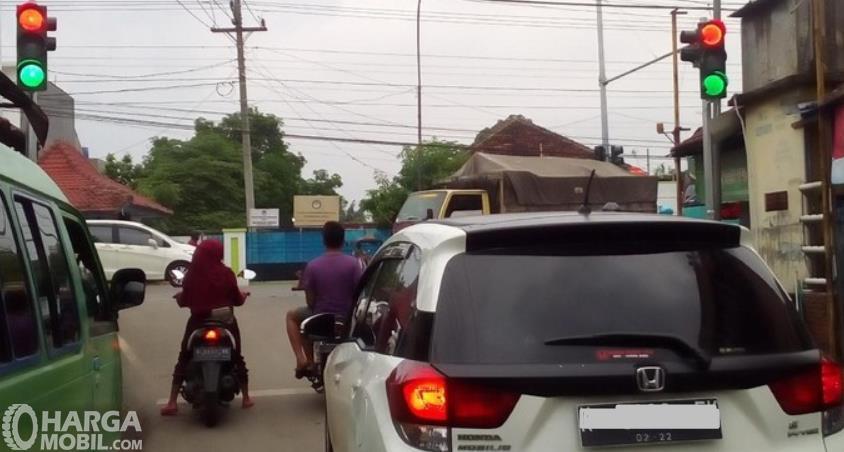 Gambar ini menunjukkan kendaraan sedang berada di lampu lalu lintas