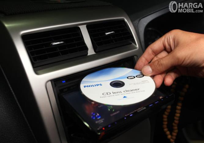 Gambar ini menunjukkan sebuah tangan memegang cd cleaner dimasukkan pada head unit