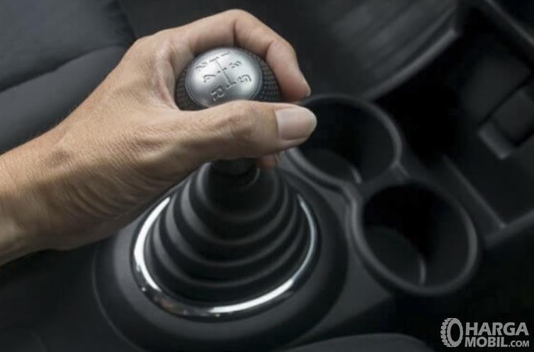 Gambar ini menunjukkan sebuah tangan memegang tuas transmisi mobil manual