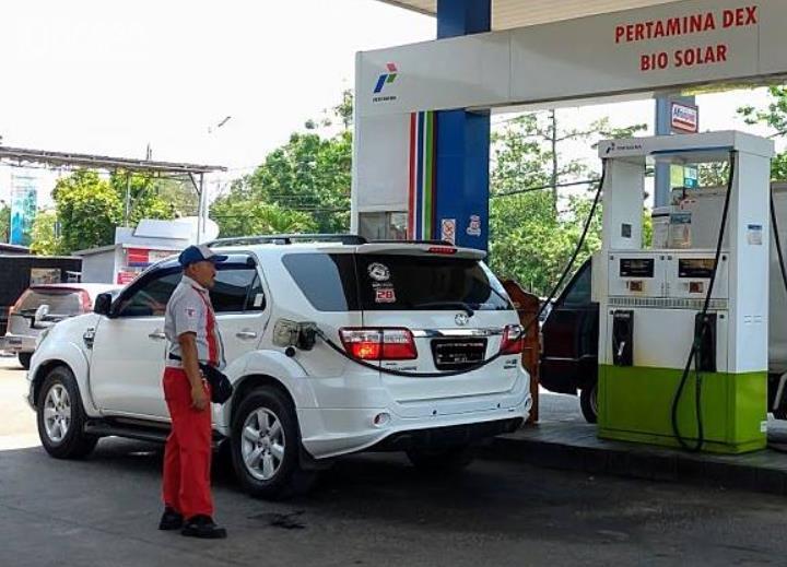Gambar ini menunjukkan petugas SPBU mengisi bahan bakar pada mobil putih
