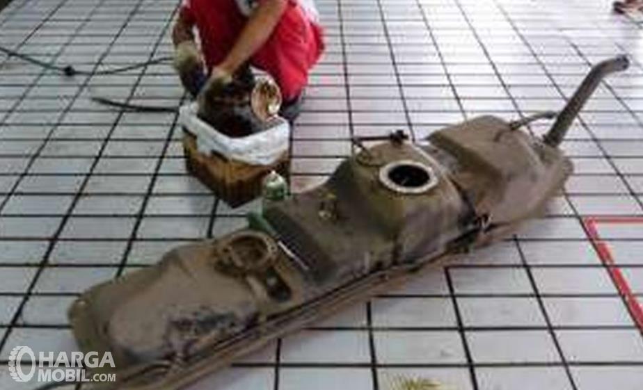 Gambar ini menunjukkan tangki bahan bakar mobil yang dilepas