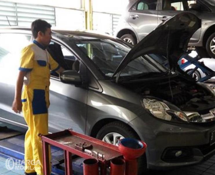 Gambar ini menunjukkan sebuah mobil sedang dibuka kapnya dan seorang mekanik