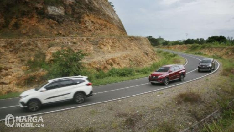 Gambar ini menunjukkan beberapa mobil melewati tikungan