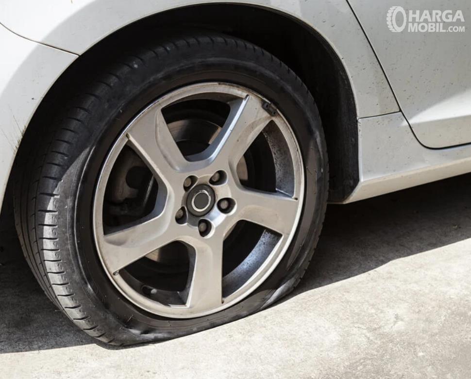Gambar ini menunjukkan ban bocor pada mobil warna putih