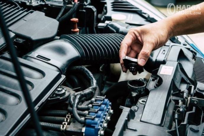 Gambar ini menunjukkan sebuah tangan membuka tutup radiator mobil