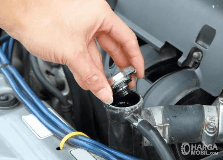 Gambar ini menunjukkan pengecekan air radiator mobil