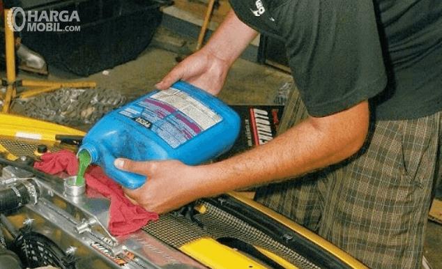 Gambar ini menunjukkan seseorang sedang mengisi air radiator mobil