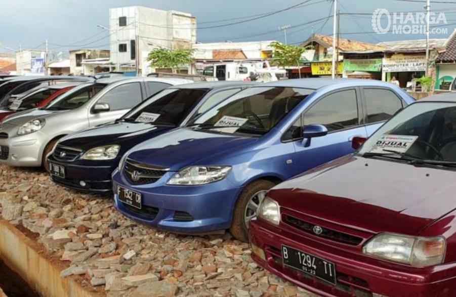 Gambar ini menunjukkan beberapa mobil diparkir berjejer dan dijual