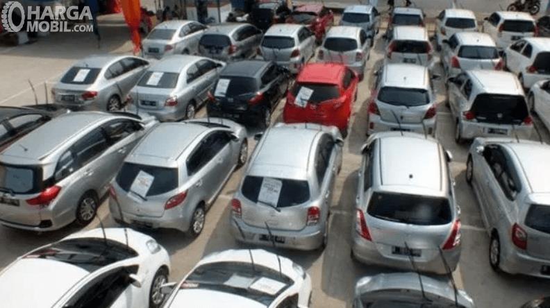Gambar ini menunjukkan banyak mobil bekas yang diparkirkan berjejer