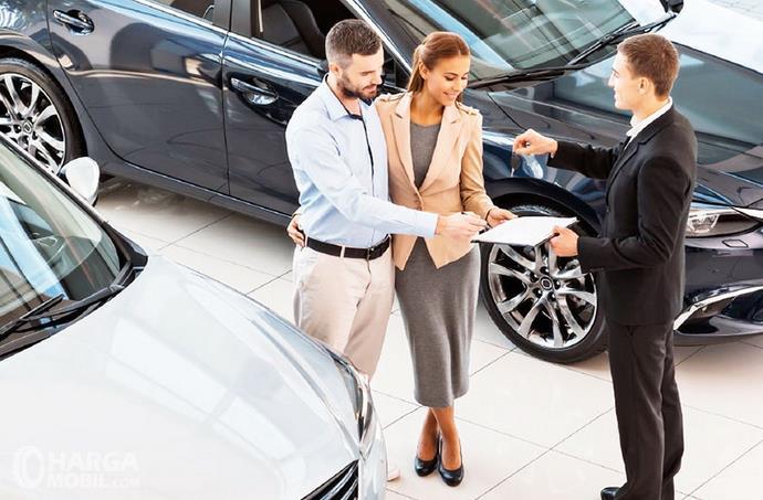 Gambar ini menunkkan 3 orang berdiri memegang dokumen di dekat mobil Hitam