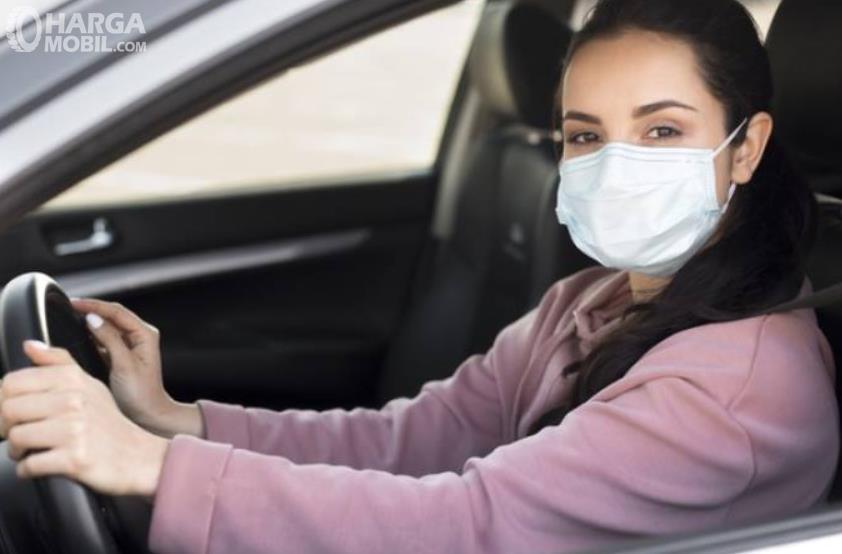 Gambar ini menunjukkan seorang wanita sengan memakai masker di dalam mobil
