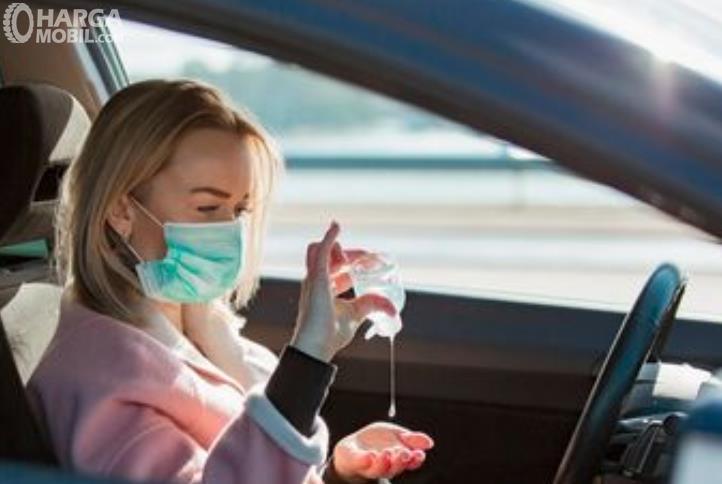 Gambar ini menunjukkan seorang wanita menggunakan masker dan pakai hand sanitizer