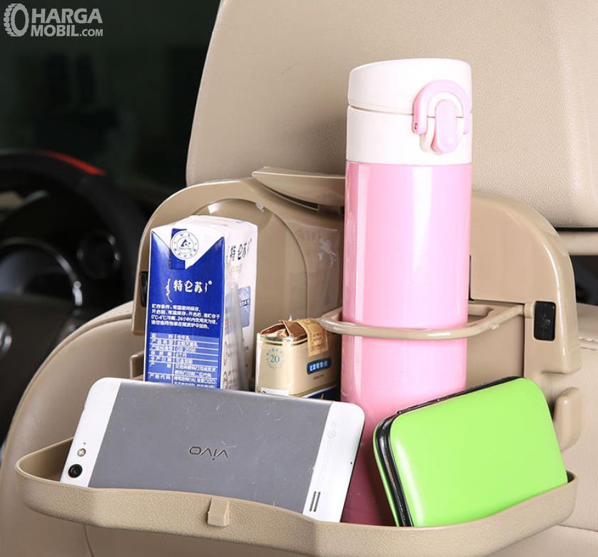 Gambar ini menunjukkan minuman dan ponsel di belakang jok mobil