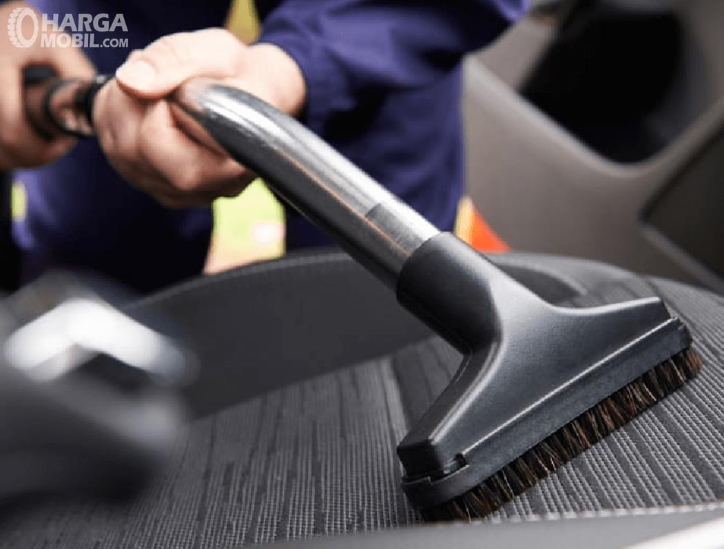 Gambar ini menunjukkan menyedot debu di kabin dengan vacuum cleaner