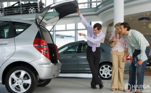 Gambar ini menunjukkan 3 orang melihat bagasi mobil