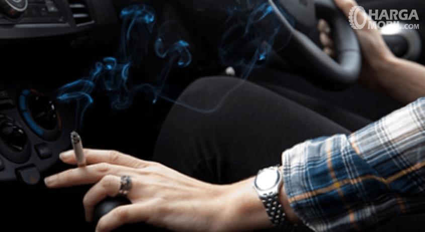 Gambar ini menunjukkan seseorang merokok di dalam mobil