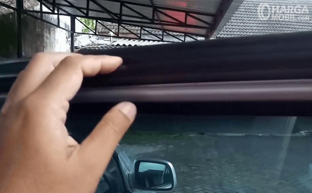 Gambar ini menunjukkan sebuah tangan memegang karet pintu mobil