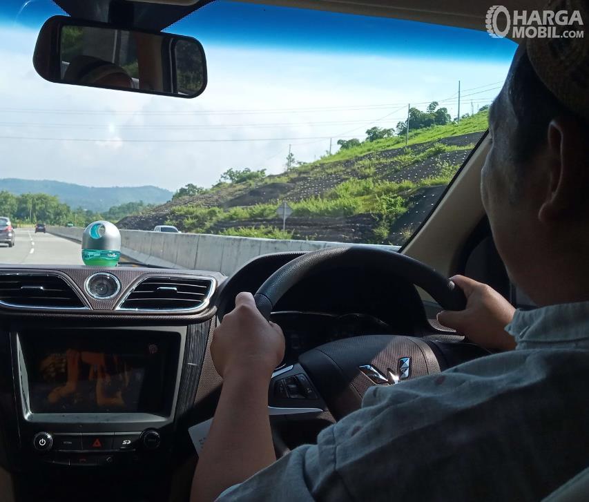 Gambar ini menunjukkan seseorang sedang mengemudi mobil