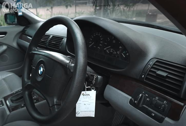 Gambar ini menunjukkan dashboard dan kemudi mobil BMW 325i 2003