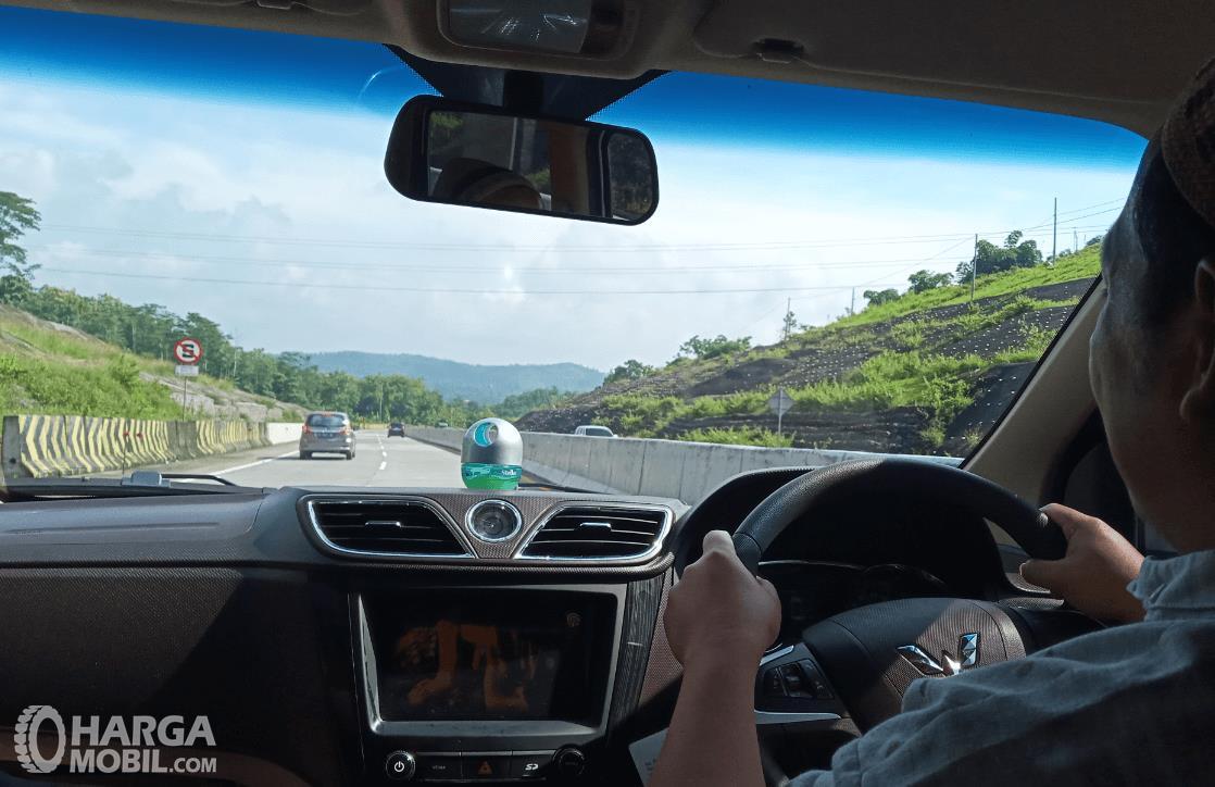 Gambar ini menunjukkan pengemudi mengemudi di jalan yang lurus